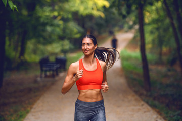 Attractive fit Caucasian brunette in sportswear and with ponytail running on trail in woods. Sunny morning in nature.