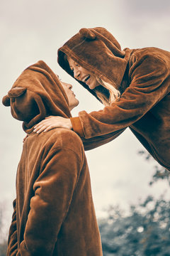 men and woman in bear costumes in the city. young couple holding hands. boy and girl are different