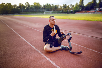 Fotomurales - Handsome caucasian sporty handicapped young man in sportswear and with artificial leg sitting on racetrack, listening music and eating banana.