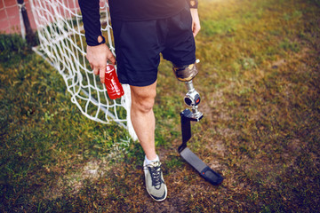 Fotomurales - Handsome sporty handicapped man in sportswear and with artificial leg while standing on football court and holding refreshment.