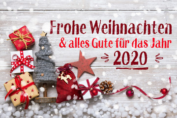 Merry Christmas and Happy New Year 2020 - Christmas Greeting Card 2019, 2020 - German language - Xmas Decoration with gift boxes and ornaments on light rustic wood