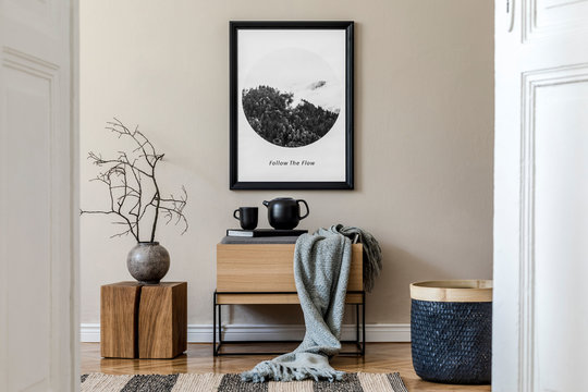 Modern scandinavian living room interior with black mock up poster frame, design commode,  leaf in vase, black rattan basket, books and elegant accessories. Template. Stylish home decor.