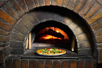 Pizza near the stone stove. Italian pizzeria restaurant.