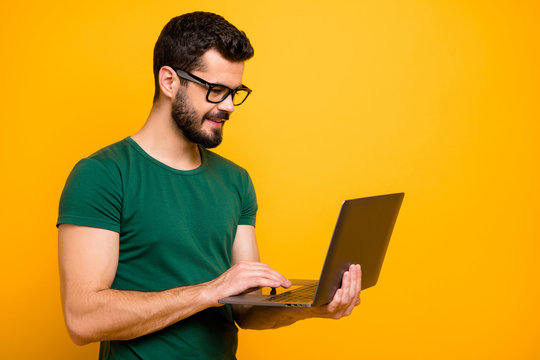 Profile side photo of positive cheerful guy use computer read study work information watch online start-up seminar wear good looking outfit isolated over yellow color background