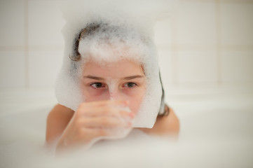 Young girl inside the bath. A little girl bathes in a bathtub with foam.