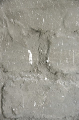 Stone wall with cement plaster sprinkled of whitewash