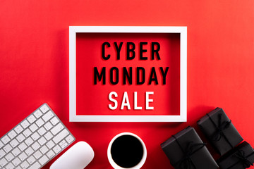 Cyber Monday Sale text on white picture frame with keyboard mouse coffee cup, gift box on black background. Shopping Online concept and Cyber Monday composition.