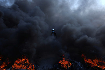 A protester walks amid a cloud of smoke from burning tires during ongoing anti-government protests in Kerbala