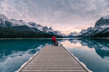 Photo sur cadre textile Canada Couple traveler relaxing on wooden pier in Maligne lake at Spirit island, Jasper national park