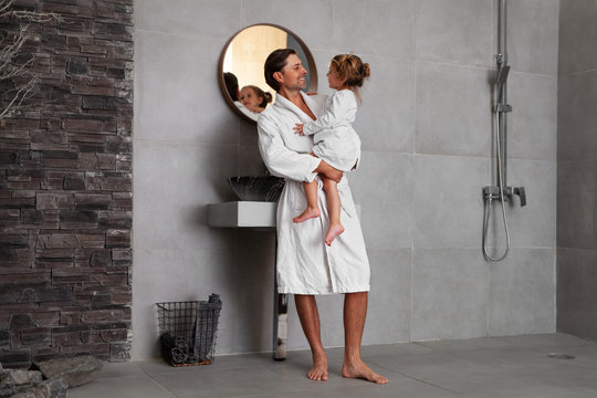 Dad and daughter looking at each other and smiling. Family in bathroom in morning. Handsome happy Father in white Bathrobe holding pretty daughter in pajama. Side View