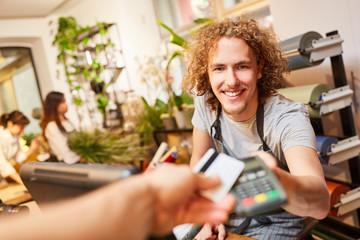 Kunde zahlt mit Kreditkarte bargeldlos beim Kassierer