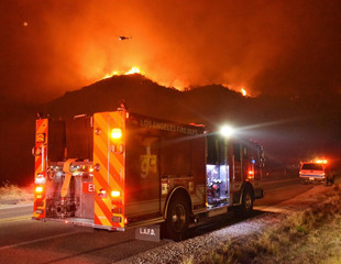 A Los Angeles Fire Department Engine is seen on Highway 154 during operations to battle flames in the nearby hillside, Santa Barbara, California