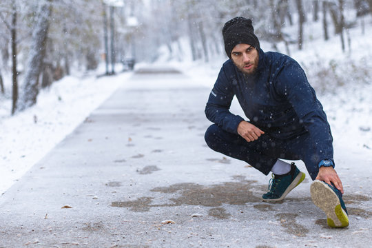 Young man stretching before running in city park at cold winter day.