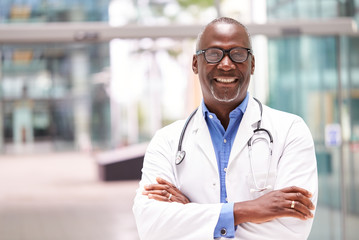 Portrait Of Male Doctor With Stethoscope Wearing White Coat Standing In Modern Hospital Building