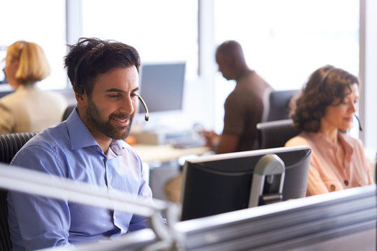Businessman Wearing Telephone Headset Talking To Caller In Customer Services Department