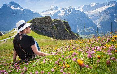 A picture of an Asian woman looking at a mountain view from a high angle in a colorful flower in Switzerland.