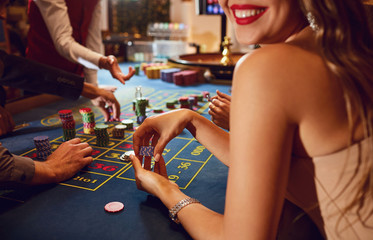 Fototapeta Chips in the hands of a female roulette player in casino background.