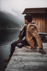 Full body shot of young male photographer in brown coat taking pictures with a small mirrorless camera while sitting on a wooden lake house deck in lake Plansee, Austria