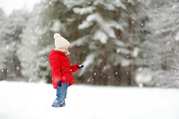 Adorable young girl having fun in beautiful winter park during snowfall. Cute child playing in a snow.