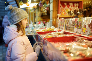 Cute young girl choosing sweets on traditional Christmas market in Riga, Latvia. Kid buying candy and cookies on Xmas.