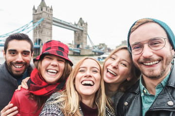 Happy friends taking selfie photo in london with Tower Bridge in background - Young people having fun with technology trends - Travel and friendship concept - Main focus on right guy face