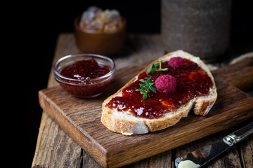 Toasted bread with sweet raspberry jam for breakfast on dark wooden background