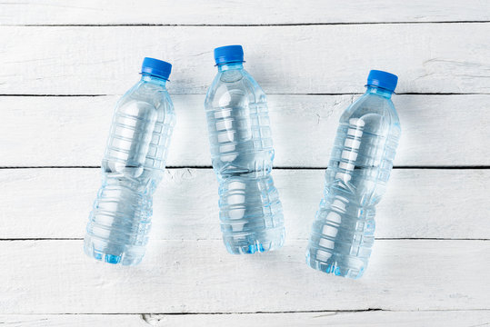 Plastic bottles with water on white wooden table. Top view