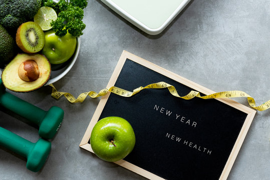 New Year for New Healthy 2020.  Fresh vegetable salad and healthy food for sport equipment for women diet slimming weight loss on wood background. Healthy and Holiday Concept