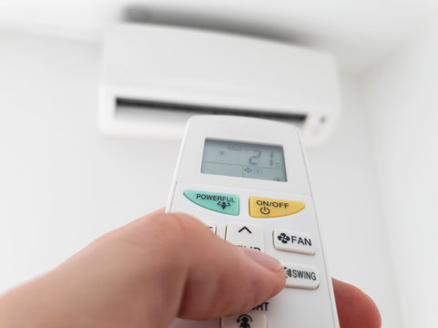 Modern airconditioner unit with a hand holding a remote.