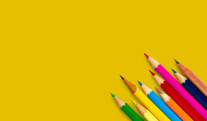 colored pencil placed on yellow paper background with copy space for your image or text.