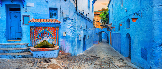 Foto auf Leinwand Marokko Fountain with drinking water on house coloured wall in blue town Chefchaouen. Morocco, North Africa