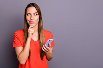 Portrait of positive cunning girl addicted social media user type sms on her cell phone think plans touch chin look copyspace wear red t-shirt isolated over grey color background