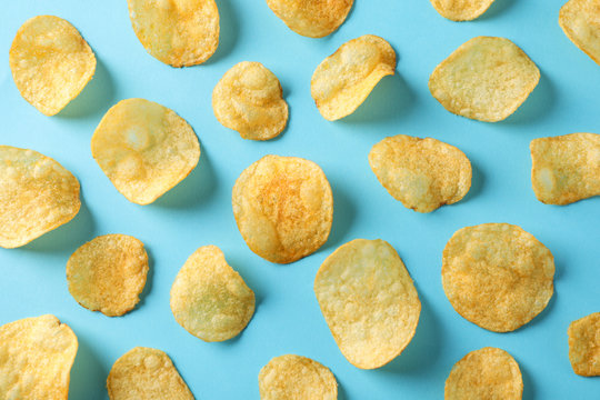 Flat lay composition with potato chips on blue background, top view