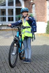 Schulkind mit Fahrrad, Helm und Warnweste zeigt Daumen hoch