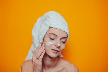 Young woman in white towel on head on the orange background. Woman in bath with clean and soft skin uses white cream.