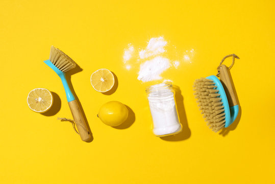 Flat lay composition with eco-friendly natural cleaners. Baking soda, salt, lemon, mustard powder and bamboo brushes on yellow background. Top view. Copy space. Flat lay. Homemade green cleaning.