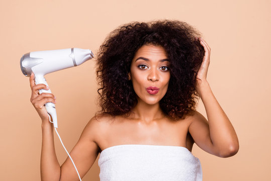 Close-up portrait of her she nice-looking attractive well-groomed cheerful feminine wavy-haired girl using electric drier preparing for disco isolated over beige pastel background