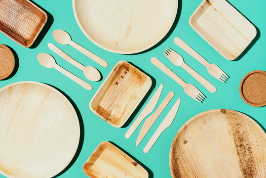 Bamboo plates, wooden spoon, fork, knife, craft paper cups on blue background. Disposable tableware from natural materials. Sustainable lifestyle concept. Eco-friendly disposable utensils
