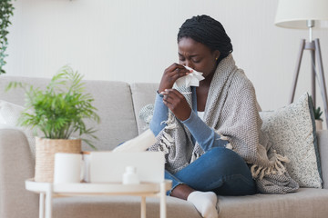 Black girl having flu, blowing nose and checking body temperature