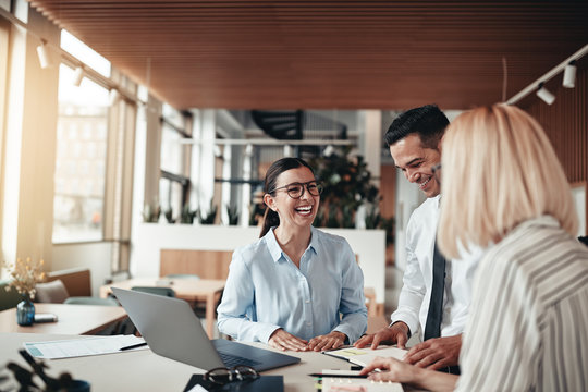 Businesspeople laughing while working at an office table