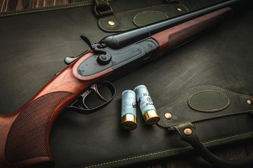 Papiers peints Chasse Classic trigger double-barreled hunting rifle on a green background. Smooth-bore hunting rifle open for reloading. Concept postcards for hunters.