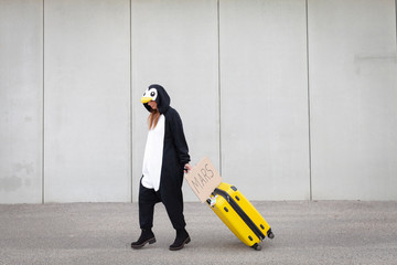 Young woman, with penguin costume and yellow suitcase, has to travel due to global warming. Symbolizes a sad penguin who has to leave his homeland because of global warming or climate change.
