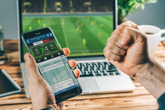 Man watching football play online broadcast on his laptop, cheering for his favourite team, making bets at bookmaker's website