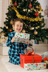 Cheerful boy opening Christmas presents at home