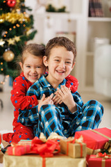 Cheerful children opening Christmas presents
