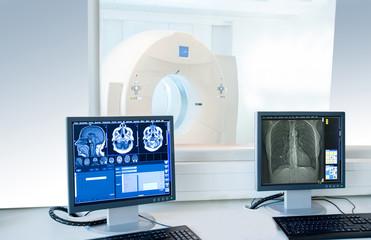 Computertomogrphie Arbeitsplatz mit Schnittbildern auf Monitoren, im Hintergrund CT Gerät in der Radiologie