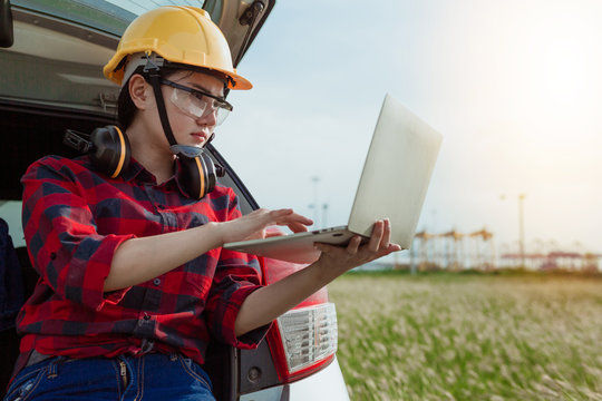 Young female engineer in protective work white wear working with notebook in wind turbines, background wind turbines, wind turbines, clean energy engineer worker concept.
