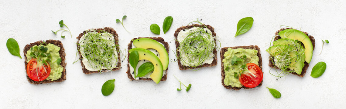 Vegetarian toasts with avocado, tofu, tomato and microgreen