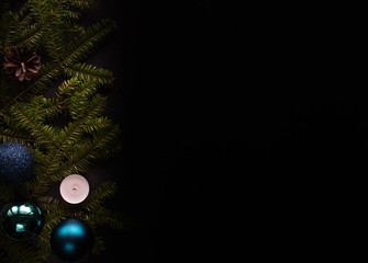 Christmas composition in the form of a frame of Christmas tree twigs, Christmas balls and a candle on a black elegant background with free space for text