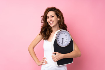 Young woman with curly hair holding a weighing machine over isolated pink background